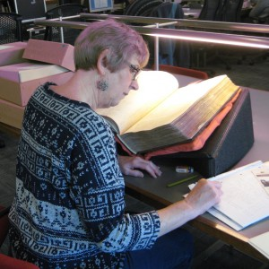 Woman reading old book on archive reading room