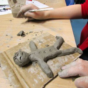 A child making a clay model of a person