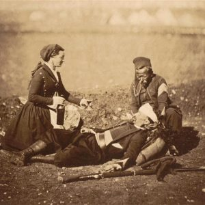 Wounded soldier held by a fellow soldier and attended by a nurse
