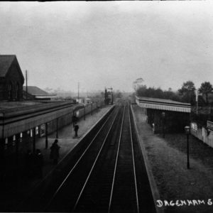 A black and white photograph looking onto the tracks of Dagenham Station, with the platforms on either side.