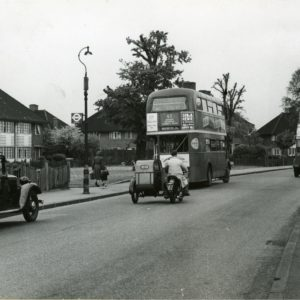 Photograph taken looking north from Ivy House Road of Gale Street, showing two buses, cars, a motorbike, and a lady walking with a pram, with houses on the left side, 1953