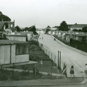 A black and white photograph showing a row of E.F.M. Prefabricated Bungalows in Lansbury Avenue, Barking, with children in the foreground.