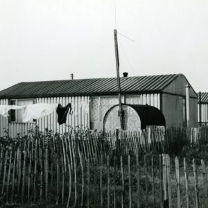 A black and white photograph of prefabricated bungalows in Lodge Avenue and Rugby Road on the site of Porters Lodge Farm, showing Second World War Anderson Shelter converted into a garden shed.