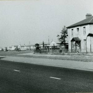 A black and white photograph of Maybell Farm, showing farmhouse (at right), Ripple Road (foreground), motor coach and lorry (left) and prefabricated houses (centre).