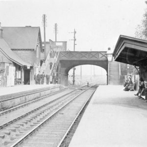 Photograph of men on either side of the platform looking towards the camera at Chadwell Heath Railway Station. Also shows the steps and bridge. Circa. 1900